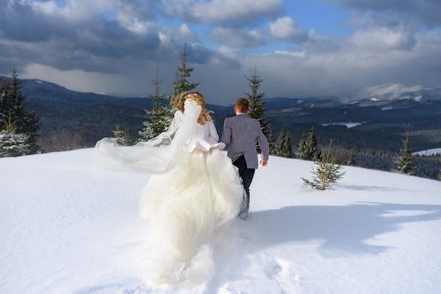 Bräutigam hält händchenhalten, die im schnee vor dem hintergrund eines winterwaldes laufen. das paar drehte der kamera den rücken zu.