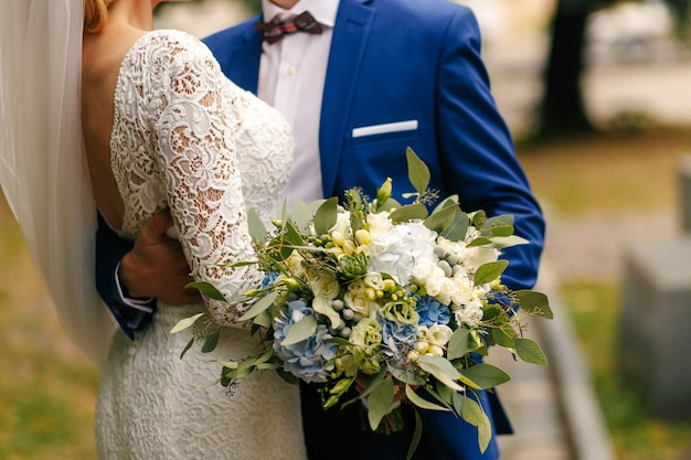 Bräutigam hält herrlichen hochzeitsblumenstrauß, während er das tender der braut umarmt