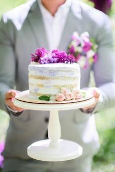 Bräutigam hält rustikalen hochzeitskuchen