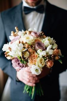 Bräutigam hält schönen hochzeitsstrauß. weiße, lila, rosa rosen.