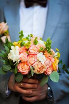 Bräutigam halten hochzeitsstrauß in der hand