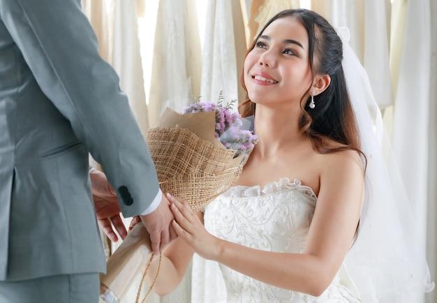 Bräutigam im grauen anzug schenkt der schönen braut hochzeitsbougue-blumen.
