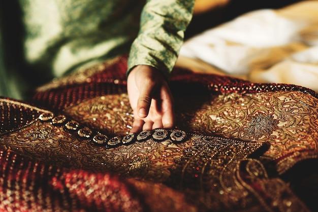 Bräutigam im grünen hemd berührt sein rotes sherwani