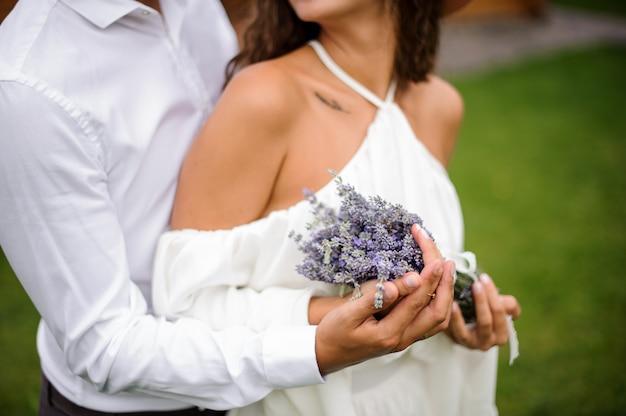 Bräutigam im weißen hemd, das braut im weißen kleid mit blumenstrauß von blumen umarmt