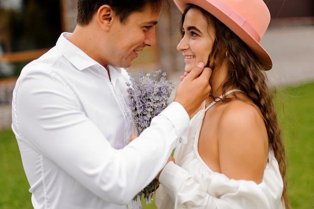 Bräutigam im weißen hemd und in der schönen braut im weißen kleid, das liebevoll einander betrachtet