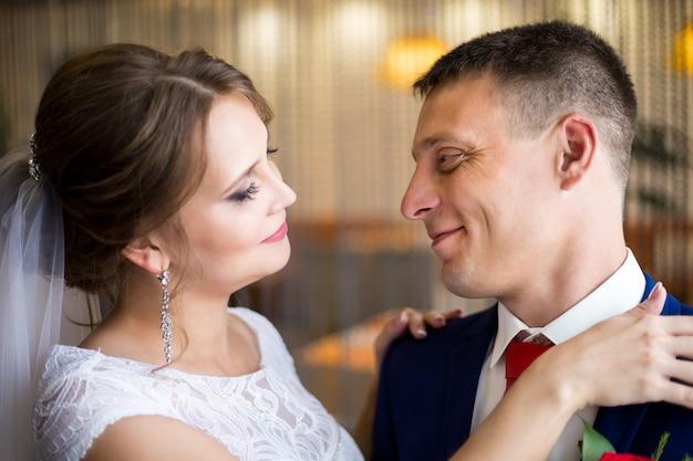 Bräutigam in einem blauen anzug und die braut in einem hochzeitskleid die jungvermählten, umarmend, posieren zusammen im café