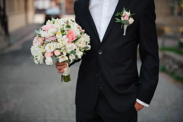 Bräutigam in einem schwarzen anzug, der einen leichten hochzeitsblumenstrauß hält
