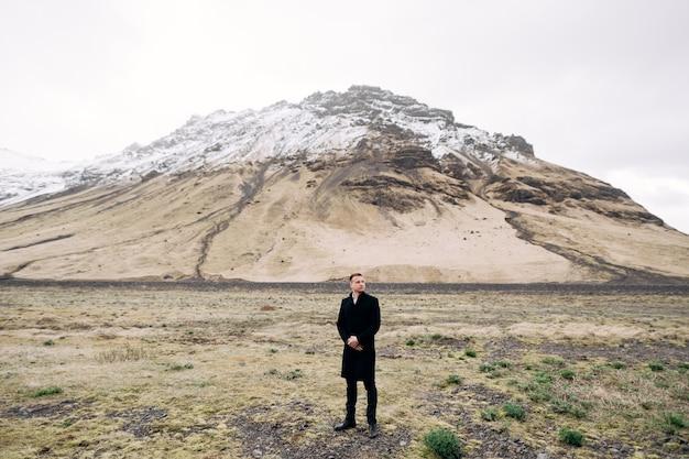 Bräutigam in einem schwarzen mantel auf einem hintergrund eines berges mit einer schneebedeckten gipfelziel-island-hochzeit