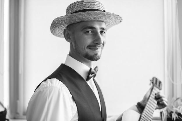 Bräutigam in landhauskleidung, die mit gitarre aufwirft