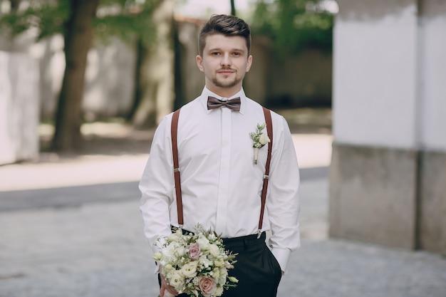 Bräutigam in strapsen mit einem blumenstrauß