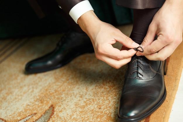 Bräutigam kleidet und bindet schuhe