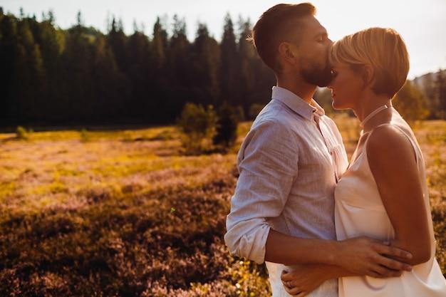 Bräutigam küsst die braut, die mit ihr auf dem feld steht