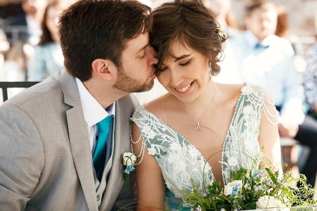Bräutigam küsst die wange der braut vor einem hochzeitsaltar