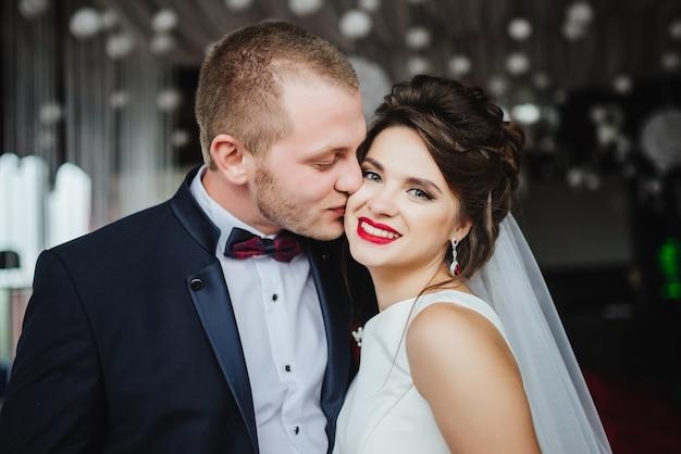 Bräutigam küsst lächelnde und glückliche braut nach hochzeitszeremonie