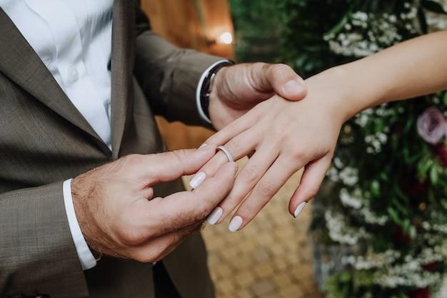 Bräutigam legt den ring auf die hand der braut bei der zeremonie