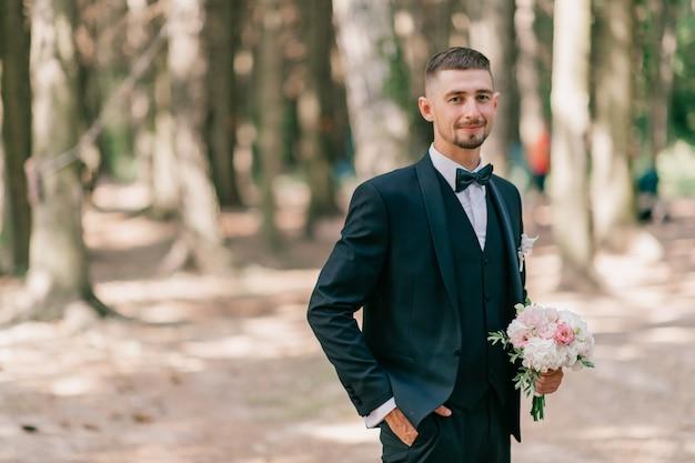 Bräutigam mit blumenstrauß, der im freien aufwirft