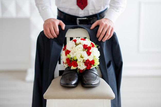 Bräutigam mit blumenstrauß und schuhen