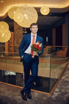 Bräutigam mit einem schönen blumenstrauß, der auf seine braut wartet