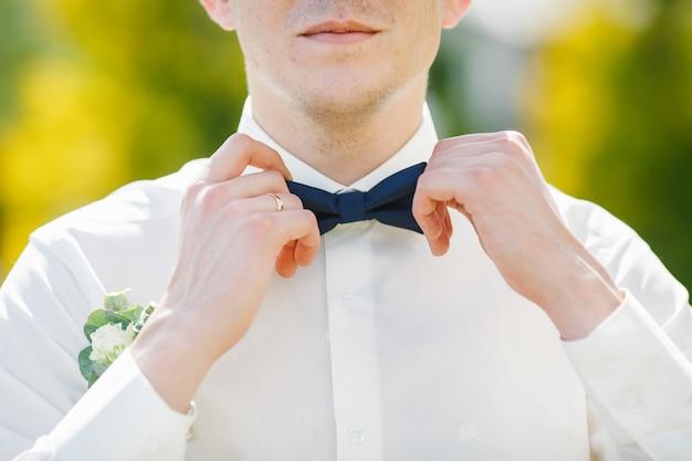 Bräutigam repariert dunkelblaue fliege auf weißem hemd