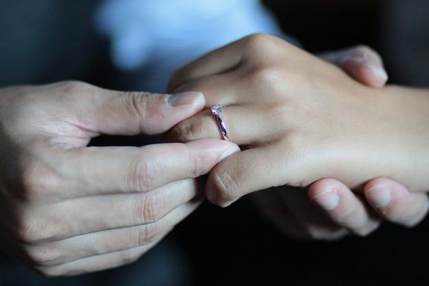Bräutigam setzt den ring auf die hand der braut herein in die thailändische hochzeitszeremonie ein.