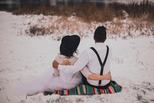 Bräutigam sitzt mit braut im weißen hochzeitskleid und im schwarzen hut auf mexikanischem nationalschleier auf schneebedecktem hügel