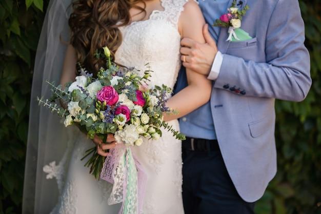 Bräutigam umarmt braut, braut, die hochzeitsstrauß hält.