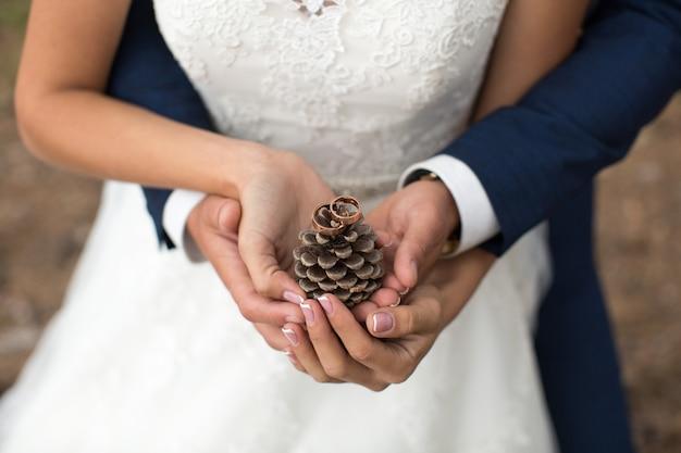 Bräutigam umarmt braut in einem kiefernwald, ihre hände halten einen klumpen
