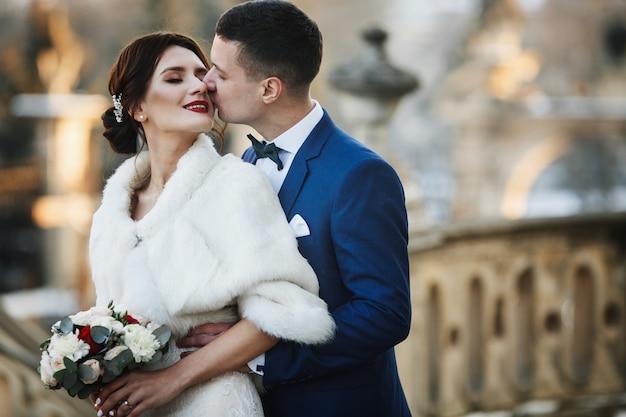 Bräutigam umarmt braut von hinten, werfend in der winterstadt auf