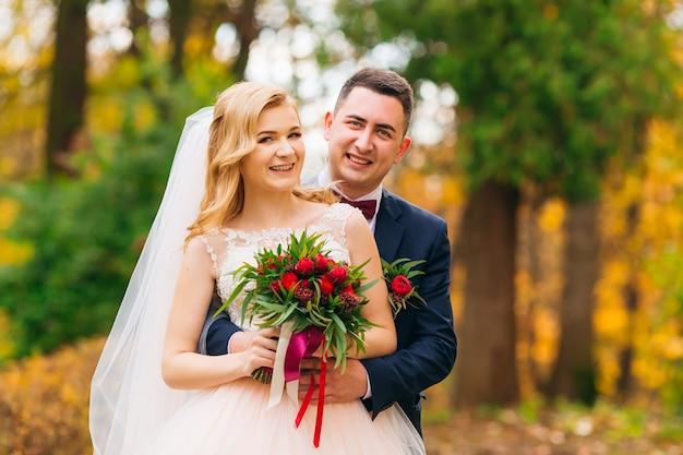 Bräutigam umarmt die braut von der rückseite braut mit hochzeitsstrauß herbstpark