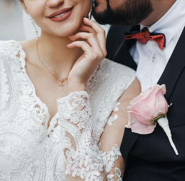 Bräutigam umarmt die zarte braut, während sie lächelt. kein gesicht