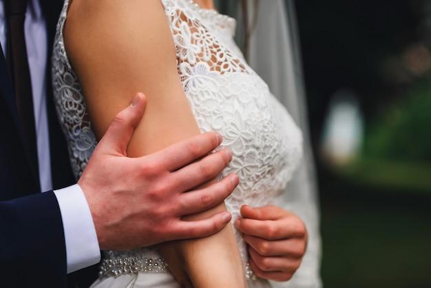 Bräutigam umarmt sanft die braut am hochzeitstag