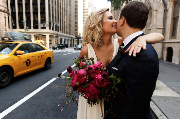 Bräutigam umarmt schöne braut mit dem roten blumenstrauß, der auf der straße von new york city steht