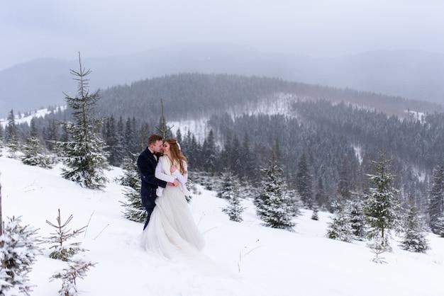 Bräutigam umarmt seine braut im verschneiten wald