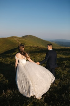 Bräutigam und braut auf dem hügel in den bergen. hochzeitspaar vor dem grünen hügel. jungvermählten genießen romantische momente in den bergen bei sonnenuntergang an einem schönen sommertag.