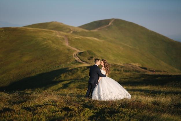 Bräutigam und braut auf dem hügel in den bergen. hochzeitspaar vor dem grünen hügel.