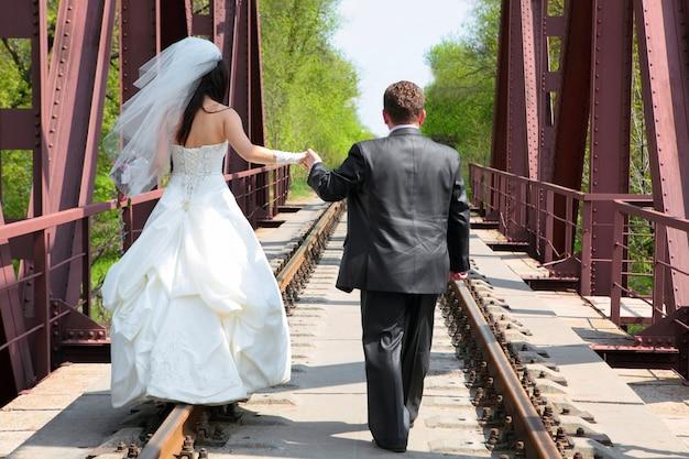 Bräutigam und braut gehen auf die eisenbahnbrücke