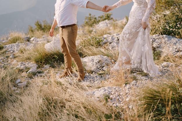 Bräutigam und braut gehen händchen haltend in den bergen