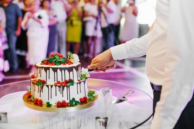 Bräutigam und braut halten ein messer, während sie hochzeitstorte schneiden