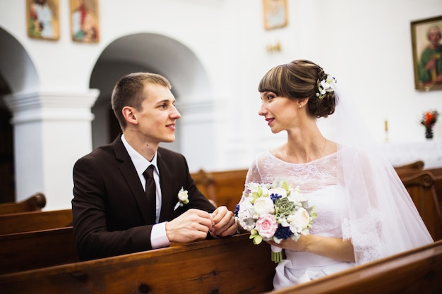 Bräutigam und braut in einem weißen kleid in der kirche. hochzeitszeremonie. glückliche familie