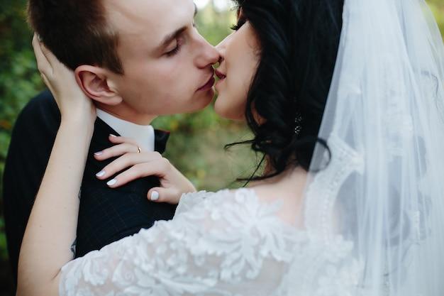 Bräutigam und braut küssen draußen stehend
