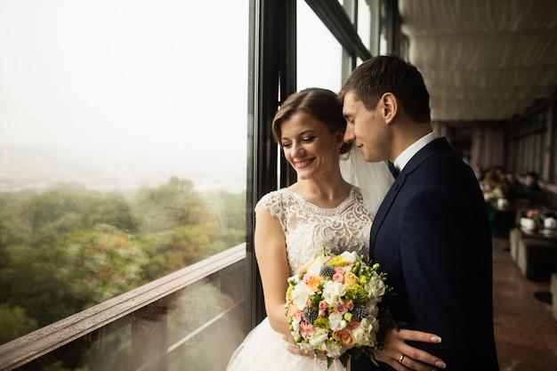 Bräutigam und braut mit einem blumenstrauß, der auf terrasse mit grüner naturansicht steht