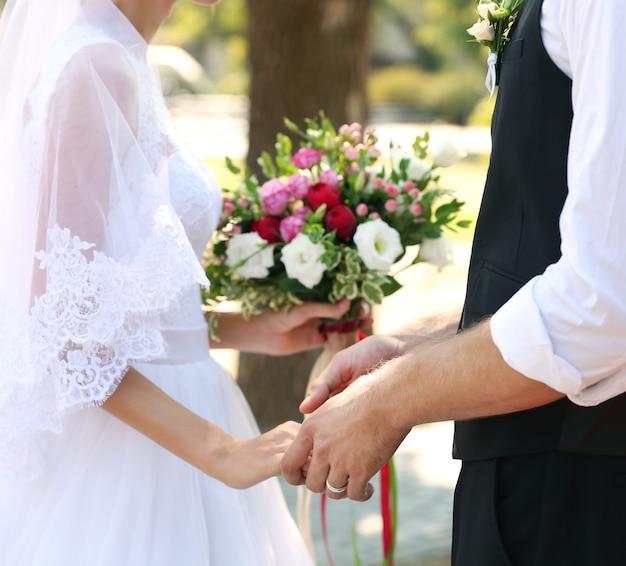 Bräutigam und braut mit hochzeitsstrauß im park, nahaufnahme