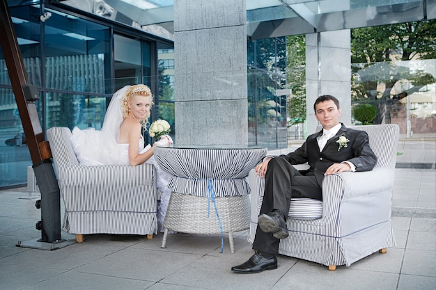 Bräutigam und die braut mit einem blumenstrauß von den rosen im café