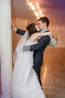 Bräutigam und die braut mit einem hochzeitsblumenstrauß stehen nahe einer weißen spalte