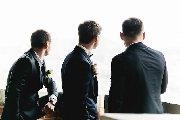 Bräutigam und trauzeugen stehen auf dem balkon