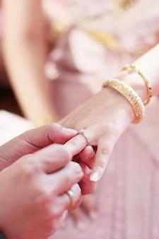 Bräutigamhände, die brauthände mit ehering in der thailändischen hochzeitszeremonie traditionell halten.