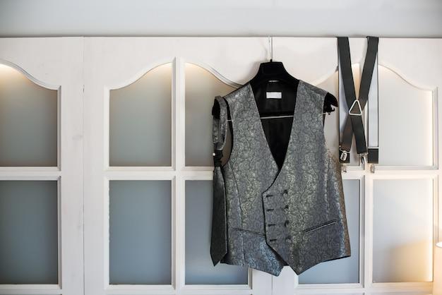 Bräutigams neue weste, krawatte und hosenträger hängen an einem kleiderbügel an einem fenster.