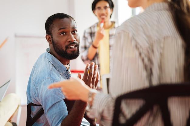 Brainstorming. aktiver begeisterter junger mann, der sich an seine kollegen wendet, während er an der diskussion während des workshops teilnimmt