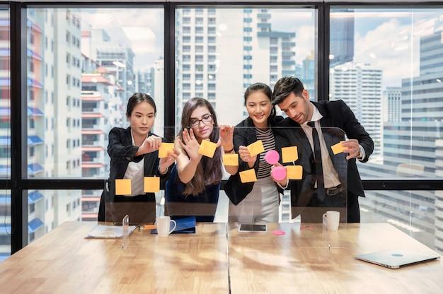 Brainstorming eines multiethnischen geschäftsteams mit paste-color-post-it-note an bord im büro