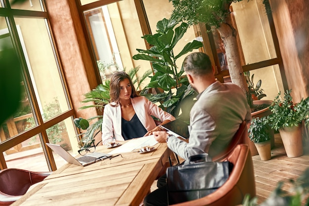 Brainstorming-geschäftsleute, die am tisch im restaurant sitzen, frau, die mann mit laptop anschaut